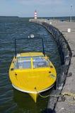 Κίτρινη βάρκα μηχανών κοντά στην αποβάθρα και το φάρο θάλασσας Στοκ Εικόνα