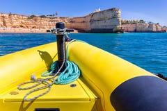 Κίτρινη βάρκα που πλέει προς τους βράχους στην ακτή Στοκ φωτογραφία με δικαίωμα ελεύθερης χρήσης