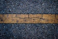 Κίτρινη γραμμή βρώμικη στη μαύρη οδική σύσταση ασφάλτου Στοκ φωτογραφία με δικαίωμα ελεύθερης χρήσης