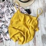 Κίτρινη θηλυκή μπλούζα σε ένα ξύλινο υπόβαθρο στοκ εικόνα με δικαίωμα ελεύθερης χρήσης