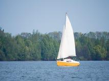 Κίτρινη και άσπρη βάρκα που πλέει με μια λίμνη μια ηλιόλουστη ημέρα Στοκ φωτογραφία με δικαίωμα ελεύθερης χρήσης