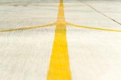 Κίτρινη κινηματογράφηση σε πρώτο πλάνο λουρίδων κατεύθυνσης σε έναν διάδρομο αεροδρομίων Στοκ Εικόνα