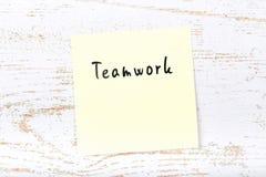 Κίτρινη κολλώδης σημείωση για το ξύλινο γραφείο με τη χειρόγραφη ομαδική εργασία κειμένων στοκ εικόνα