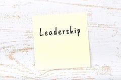 Κίτρινη κολλώδης σημείωση για το ξύλινο γραφείο με τη χειρόγραφη ηγεσία κειμένων στοκ εικόνα με δικαίωμα ελεύθερης χρήσης