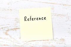 Κίτρινη κολλώδης σημείωση για το ξύλινο γραφείο με τη χειρόγραφη αναφορά κειμένων στοκ εικόνα με δικαίωμα ελεύθερης χρήσης