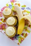 Κίτρινη μπανάνα εναντίον του κίτρινου cupcake Στοκ Φωτογραφία