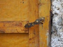 Κίτρινη ξύλινη εκλεκτής ποιότητας πόρτα στον άσπρο τοίχο του σπιτιού, που κλείνουν σε έναν σύρτη μετάλλων Στοκ Φωτογραφίες