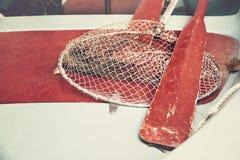 Κίτρινη ξύλινη πλέοντας βάρκα με τα κόκκινα κουπιά και αλιεία με δίχτυα για την αλιεία στοκ φωτογραφία με δικαίωμα ελεύθερης χρήσης
