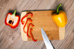 Κίτρινη πάπρικα στο τέμνον μαχαίρι μορίων πινάκων Λουρίδες κόκκινων πιπεριών και ξύλινο υπόβαθρο μορίων μαχαιριών Στοκ φωτογραφίες με δικαίωμα ελεύθερης χρήσης