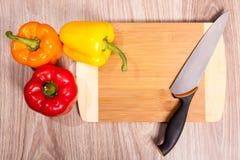 Κίτρινη πάπρικα στο τέμνον μαχαίρι μορίων πινάκων Λουρίδες κόκκινων πιπεριών και ξύλινο υπόβαθρο μορίων μαχαιριών Στοκ Φωτογραφίες