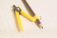 Κίτρινη πυξίδα σχεδίων σε χαρτί γραφικών παραστάσεων Στοκ εικόνες με δικαίωμα ελεύθερης χρήσης