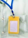 Κίτρινη πλαστική περίπτωση της ένωσης ετικετών λαιμών στην πράσινη τσέπη πουκάμισων Στοκ Εικόνες
