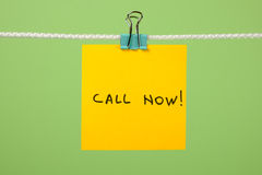 """Κίτρινη σημείωση εγγράφου για τη σκοινί για άπλωμα με το κείμενο """"Call τώρα! † Στοκ Φωτογραφίες"""
