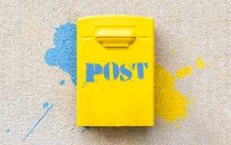 Κίτρινη ταχυδρομική θυρίδα ταχυδρομείων στον επικονιασμένο τοίχο Στοκ Εικόνα
