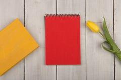 Κίτρινη τουλίπα λουλουδιών, κενά κόκκινα σημειωματάριο και βιβλίο σε έναν άσπρο ξύλινο πίνακα Στοκ Φωτογραφίες