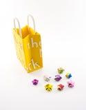 Κίτρινη τσάντα εγγράφου αγορών κρέμας με το χέρι - γίνοντα αστέρια στο λευκό Στοκ Φωτογραφία