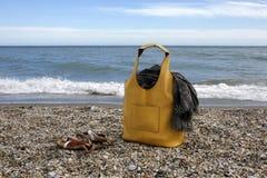 Κίτρινη τσάντα, μαντίλι και σανδάλια δέρματος στην παραλία Στοκ Εικόνες