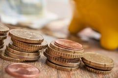 Κίτρινη piggy τράπεζα στα ευρο- νομίσματα και τραπεζογραμμάτια στο wo Στοκ φωτογραφία με δικαίωμα ελεύθερης χρήσης