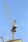 Κίτρινοι γερανοί στο εργοτάξιο οικοδομής με το μπλε ουρανό Στοκ Εικόνες