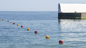 Κίτρινοι και κόκκινοι σημαντήρες στη θάλασσα κοντά στην αποβάθρα Στοκ Εικόνα