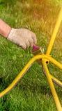 Κίτρινοι πάγκοι πλαισίων σιδήρου χρωμάτων χρωμάτων χεριών ατόμων ` s στον κήπο σε ένα πράσινο υπόβαθρο μια ηλιόλουστη ημέρα Το κά Στοκ φωτογραφίες με δικαίωμα ελεύθερης χρήσης