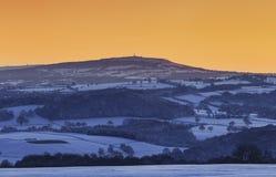 Κίτρινος ασυννέφιαστος ουρανός ηλιοβασιλέματος πέρα από τους φυσικούς λόφους στο χειμώνα στοκ φωτογραφίες