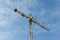Κίτρινος γερανός κατασκευής στο υπόβαθρο μπλε ουρανού Ηλιόλουστη ημέρα, hor Στοκ Εικόνες