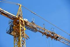 Κίτρινος γερανός πύργων χτίζοντας ένα σπίτι ενάντια σε έναν μπλε ουρανό Στοκ Φωτογραφίες