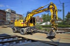 Κίτρινος εκσακαφέας στη μετακίνηση στο εργοτάξιο οικοδομής Στοκ Φωτογραφίες
