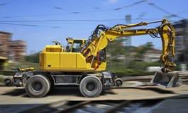 Κίτρινος εκσακαφέας στη μετακίνηση στο εργοτάξιο οικοδομής Στοκ φωτογραφία με δικαίωμα ελεύθερης χρήσης