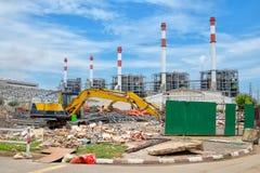 Κίτρινος εκσκαφέας ενάντια στο εργοτάξιο οικοδομής Στοκ Εικόνες