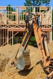 Κίτρινος εκσκαφέας που λειτουργεί στη νέα επισκευή οικοδόμησης ανακαίνισης κατασκευής Στοκ Φωτογραφίες