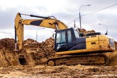 Κίτρινος εκσκαφέας που λειτουργεί στην άμμο, η οδοποιία Στοκ Εικόνα