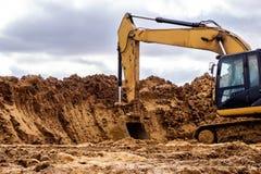 Κίτρινος εκσκαφέας που λειτουργεί στην άμμο, η οδοποιία Στοκ Φωτογραφία
