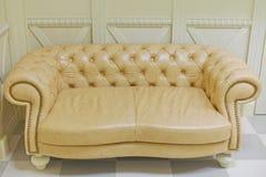 Κίτρινος εκλεκτής ποιότητας καναπές στο εσωτερικό Στοκ Φωτογραφίες