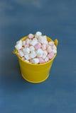 Κίτρινος κάδος με marshmallow στο μπλε ξύλινο υπόβαθρο Στοκ Εικόνες