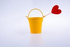 Κίτρινος κάδος χρώματος και κόκκινη μορφή καρδιών Στοκ Εικόνες