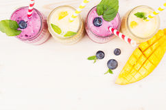 Κίτρινος και ιώδης καταφερτζής φρούτων στα βάζα γυαλιού με το άχυρο, τα φύλλα μεντών, τις φέτες μάγκο και το μούρο, τοπ άποψη Στοκ Εικόνα