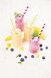 Κίτρινος και ιώδης καταφερτζής φρούτων στα βάζα γυαλιού με το άχυρο, φύλλα μεντών, φέτες μάγκο, μούρο Στοκ Εικόνες
