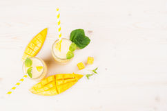 Κίτρινος καταφερτζής φρούτων μάγκο στα βάζα γυαλιού με το άχυρο, φύλλα μεντών, φέτες μάγκο, τοπ άποψη Άσπρο ξύλινο υπόβαθρο πινάκ Στοκ εικόνες με δικαίωμα ελεύθερης χρήσης