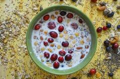 Κίτρινος πίνακας με το πράσινο σύνολο κύπελλων Oatmeal, των σπόρων chia, των φρέσκων μούρων, των σπόρων, των καρυδιών και του γάλ στοκ φωτογραφία