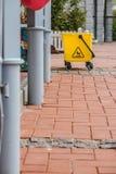 Κίτρινος πλαστικός κάδος στην οδό, έδαφος που γίνεται από τα τούβλα Στοκ Φωτογραφίες