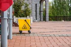 Κίτρινος πλαστικός κάδος στην οδό, έδαφος που γίνεται από τα τούβλα Στοκ Εικόνα