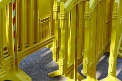Κίτρινος πλαστικός φράκτης εμποδίων πέρα από έναν δρόμο ασφάλτου Στοκ Φωτογραφία