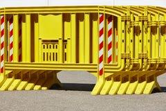 Κίτρινος πλαστικός φράκτης εμποδίων πέρα από έναν δρόμο ασφάλτου Στοκ εικόνες με δικαίωμα ελεύθερης χρήσης