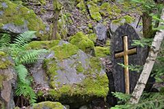 Κίτρινος σταυρός σε ξύλινη περίπτωση στις πέτρες σε ένα δάσος Στοκ Φωτογραφίες