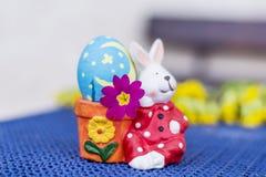 Κίτρινο αυγό αυγών λαγουδάκι Πάσχας με το ρόδινο λουλούδι Στοκ Φωτογραφίες