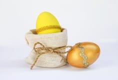 Κίτρινο αυγό Πάσχας στην τσάντα καμβά και το χρυσό αυγό Στοκ φωτογραφία με δικαίωμα ελεύθερης χρήσης