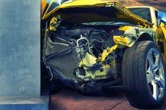 Κίτρινο αυτοκίνητο πολυτέλειας που συντρίβεται στον πόλο στην οδική κινηματογράφηση σε πρώτο πλάνο Η τσαλακωμένη μηχανή Στοκ Φωτογραφία