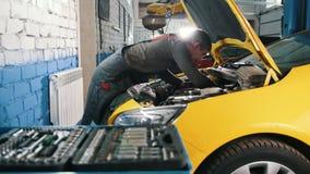 Κίτρινο αυτοκίνητο στην αυτόματη υπηρεσία γκαράζ - ανοικτή κουκούλα - επισκευή μηχανών απόθεμα βίντεο
